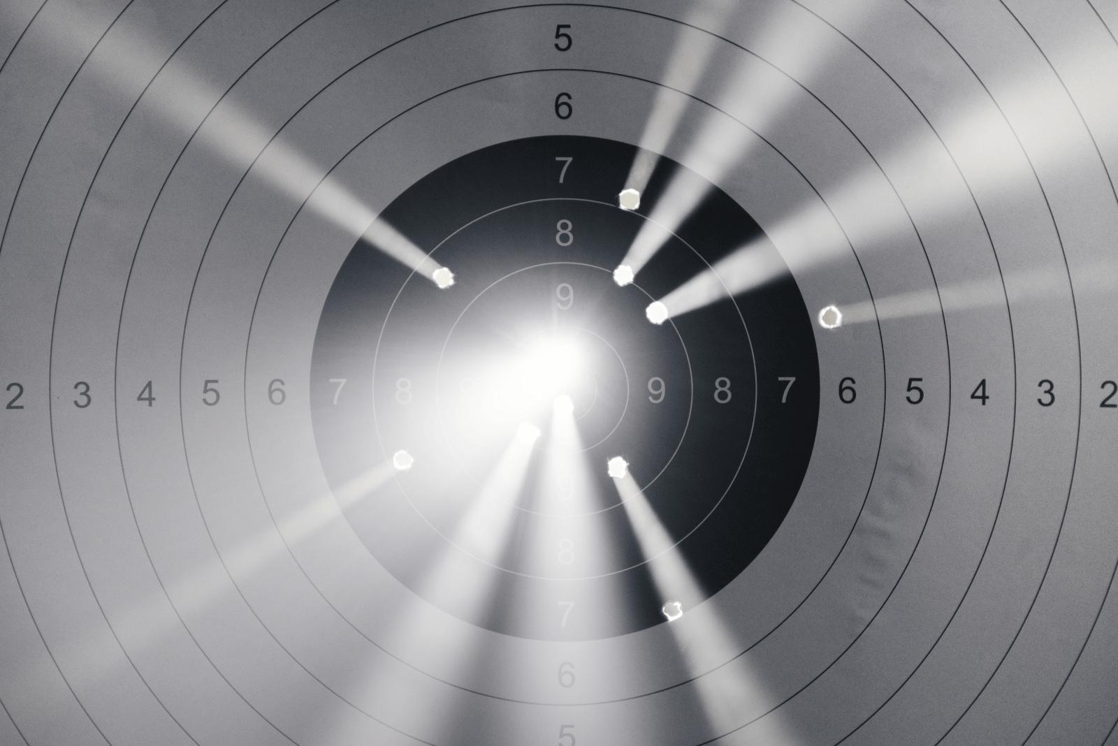 Das Foto zeigt eine durchlöcherte schwarz-weiße Zielscheibe. Durch die Schusslöcher sind Lichtstrahlen von einer nicht zu sehenden Lichtquelle hinter der Zielscheibe zu erkennen. Die Nummern der Zielscheibe gehen von 1-10, wobei sich die Nummer 1 ganz außen befindet und die Nummer 10 in der Mitte. Die Nummer 10 ist auf Grund der Löcher und des Lichtes nicht zu erkennen. Ab der Zahl 7 ist der Hintergrund der Kreise nicht mehr weiß, sondern schwarz.