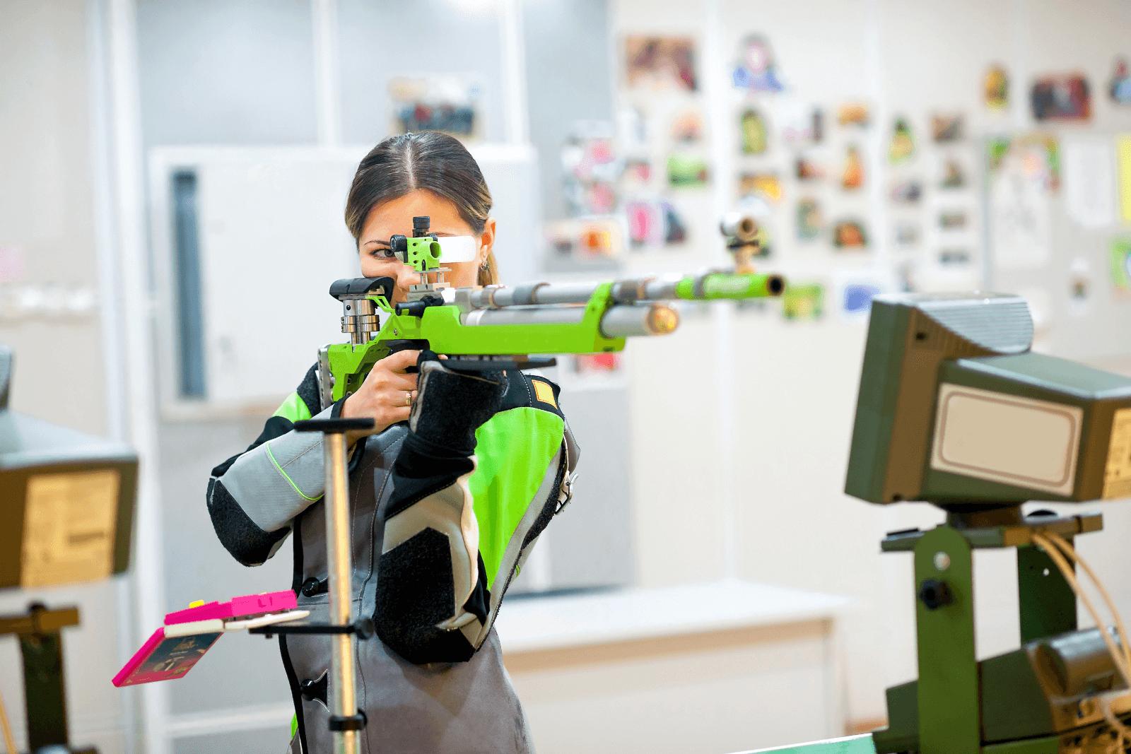 Das Bild zeigt eine freistehenden Schützin an einem Schießstand in einer Schießhalle. Die Schützin hat ein grün-graues Gewehr angelegt und zielt. Sie trägt eine grau-schwarze Jacke mit grünen Verstärkungen an den Armen. Im Hintergrund ist verschwommen eine Wand der Schießhalle zu erkennen.