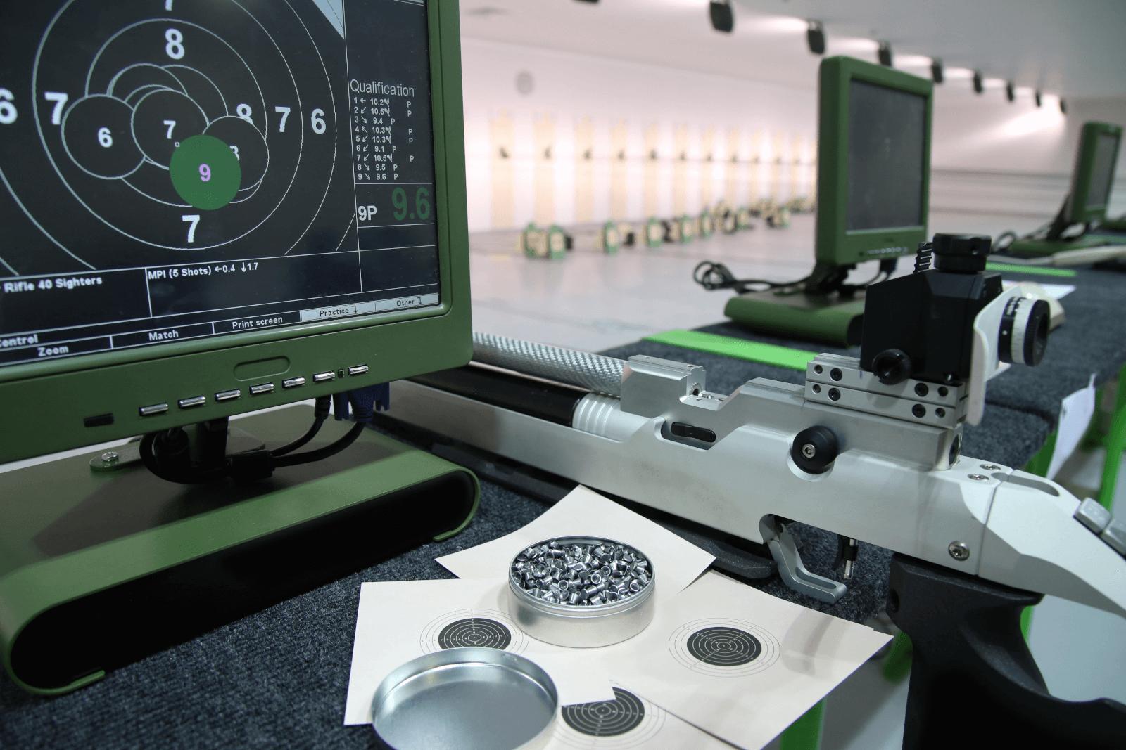 Das Bild zeigt einen Schießstand mit den Geräten von SUIS. Im Vordergrund des Bildes ist ein Monitor von SUIS, Patronenhülsen und ein silbernes Luftgewehr zu erkennen. Auf dem Bildschirm des Monitors werden die Treffer des Schützen angezeigt. Im Hintergrund des Bildes sieht man weitere Monitore, sowie die Schießhalle verschwommen.
